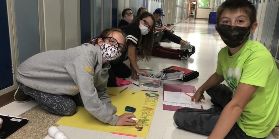 Grade 7 students spread out in the hallway to work on their science posters